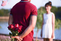 A young man hides behind a rose Royalty Free Stock Photo
