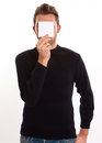 Young man hiding behind a note with blank paper his face Royalty Free Stock Images