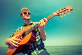 Young man hipster playing guitar by sea ocean. Royalty Free Stock Photo