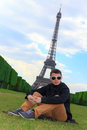 Young man hipster sitting near the eiffel tower france sits on champ de mars la tour in paris Stock Photo
