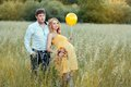 Young man and his pregnant wife standing in the field men looking into distance girl is holding a toy balloon Royalty Free Stock Image