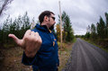 Young man hitchhiking on a finnish country road near the woods Royalty Free Stock Photo