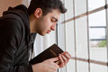 Young man holding bible praying window Royalty Free Stock Photos