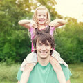 Young man holding blonde little girl on shoulders Royalty Free Stock Photography