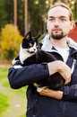 Young man holding a cat finnish female Royalty Free Stock Images