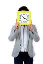 Young man holding clock covering his face over white background Royalty Free Stock Image