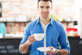 Young man holding cup of coffee in cafe Royalty Free Stock Images
