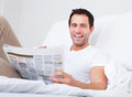 Young Man Holding Cup In Hand Reading Newspaper Royalty Free Stock Photo