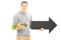 Young man holding a dish with vegetables and big black arrow poi pointing right isolated on white background Stock Photos