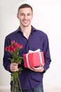 Young man holding flowers and gift box Stock Photography