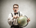 Young man holding a globe surprised and indicating place Stock Photos