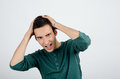 Young man holding his head frowning with worry screaming. Stock Photography