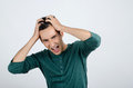 Young man holding his head frowning with worry screaming. Royalty Free Stock Images