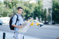 Young man holding a map yourng tourist reads in city Stock Photography