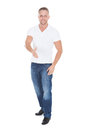Young man holding out his hand in greeting jeans and a white top Royalty Free Stock Photo