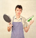 Young man holding pan and iron wearing apron Stock Photo