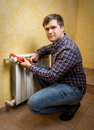 Young man holding pliers and installing radiator valve Royalty Free Stock Photo