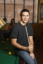 Young man holding pool stick. Royalty Free Stock Photo
