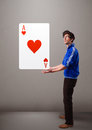 Young man holding a red heart ace attractive Royalty Free Stock Image