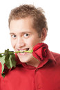 Young man holding a red rose in his mouth Royalty Free Stock Image