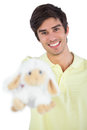 Young man holding sheep plush