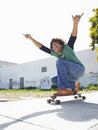 Young man holding skateboard full length of with arms raised on outdoors Royalty Free Stock Images