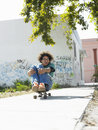 Young man holding skateboard full length of sitting while skateboarding on urban street Stock Image