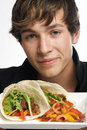 Young man holding up plate of tacos Royalty Free Stock Photos
