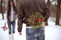 Young man holding winter bouquet behind his back dating girlfriend and celebrating valentines day. Couple in love outdoor.
