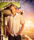 Young man home conceptual portrait of a standing in front of a small with usa flag waving and dramatic skyline behind him in warm Royalty Free Stock Image