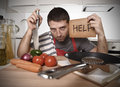 Young man at home kitchen in cook apron desperate in cooking stress Royalty Free Stock Photo
