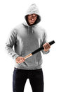 Young man with hood over his head holding a baseball bat symboli symbolizing crime isolated on white background Stock Photo