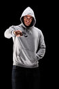 Young man with hood over his head holding a gun symbolizing crim crime isolated on black background Stock Images