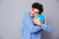 Young man hugging globe