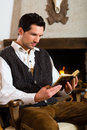 Young man in a hunter s cabin reading the bible traditional mountain hut with fireplace Stock Photography