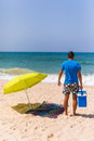 Young man with ice bar cooler under solar umbrella on a beach ne Royalty Free Stock Photo