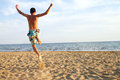 Young man jumping on beach Stock Images