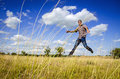 Young man jumping on dry meadow Royalty Free Stock Photo