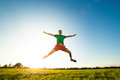 Young man jumping on meadow with dandelions Royalty Free Stock Photo