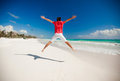 Young man jumping and raising his arms up on the beach this image has attached release Royalty Free Stock Photo