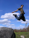 Young man jumping from stone Stock Photography