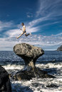 Young man is jumping on stone, Kannesteinen, Norway Royalty Free Stock Photo