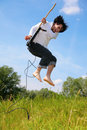 Young man jumps with guitar on grass Royalty Free Stock Photo
