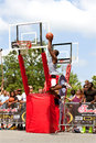 Young man jumps high in outdoor basketball slam dunk contest athens ga usa august a elevates above the rim to a the competition of Stock Photos