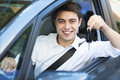 Young man with keys to new car sitting in Royalty Free Stock Photo