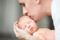 Young man kissing a newborn, he holds in his palms Royalty Free Stock Photo