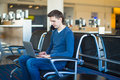 Young man with a laptop at the airport while waiting his flight Royalty Free Stock Photos
