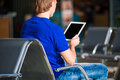 Young man with laptop at the airport while waiting Royalty Free Stock Photo