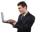 Young man with a laptop in business suit smiling to something on his computer Royalty Free Stock Photos