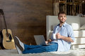 Young man with laptop and cup sitting on carpet and looking away Royalty Free Stock Photo